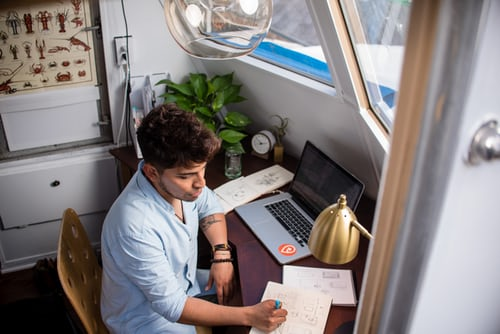 man sitting at desk with computer